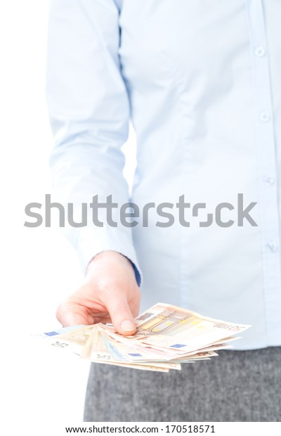 A hand of a young businesswoman holding a lot of money in Euro banknotes and giving them to the camera, closeup image.