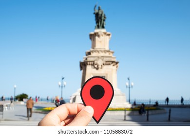 the hand of a young caucasian man with a red marker at the end of the popular Rambla Nova street, in Tarragona, Spain, highlighting the monument to Roger de Lluria and the Mediterranean Balcony