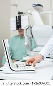 Hand of young contemporary ophthalmologist turning knob on examination equipment while checking eyesight of senior man