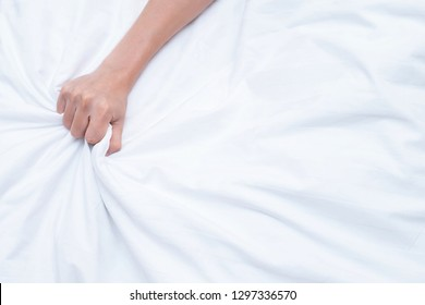 hand of Young couple lover sex intimacy pulling white sheets in ecstasy on the bed, orgasm. Concept about love, sex . Leave copy space for writing messages.