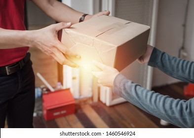 hand of young delivery service man in red uniform with woman customer receiving parcel post box from courier at home, cargo shipping, express delivery service, online shopping and logistics concept