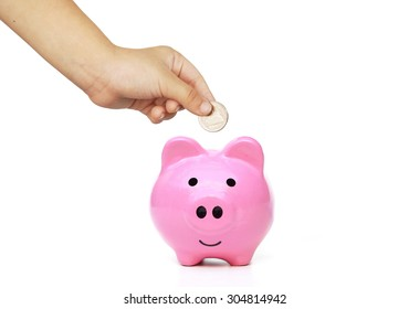 hand of a young female child putting a coin into a pink piggy bank - kid saving money for future concept