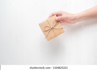 hand of a young girl holding a gift box on a white wooden background