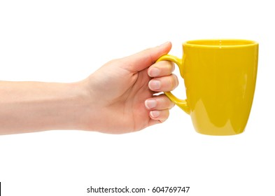 hand of young girl holding yellow cup. Isolated on white background