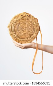 The hand of a young girl holds a fashionable natural rattan bag against the background of a light wall. Rattan handbag, ecobags from Bali. Eco-bag concept, trendy bamboo bag. Copy space