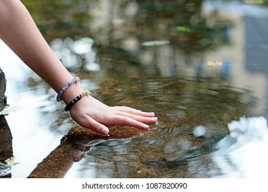 hand of young girl touching water