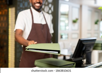 Hand of young happy waiter in brown apron passing you menu in green cover while standing by his workplace with comuter in restaurant