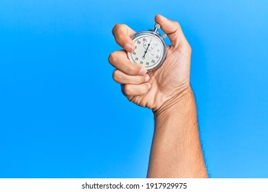 Hand of young hispanic man using stopwatch over isolated blue background.