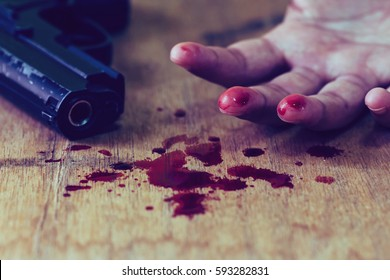 hand of young man and gun with red blood on wooden floor, committed suicide , conceptual image