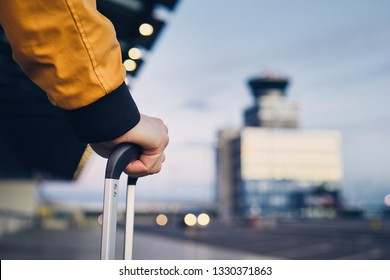 Hand of the young man holding luggage against airport terminal.
