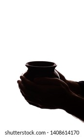 The hand of a young man holds a ceramic pot - silhouette, concept