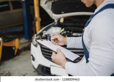 Hand of young man mechanic holding clipboard checklist the car at service center repair