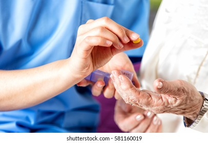 Hand of young nurse giving medical pill to elderly woman.
