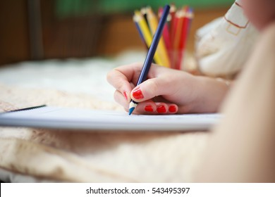 Hand of young woman drawing art picture by colorful crayons (color toned image)