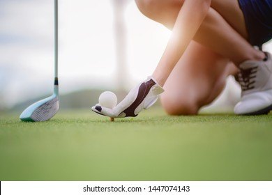 hand of young woman golf player holding golf ball push on wooden tee, ready to hit the ball to the destination target
