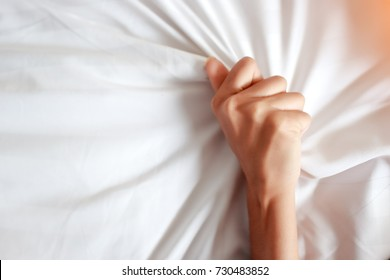 hand of young woman having sex on bedroom
