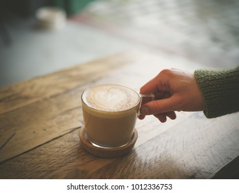 The hand of a young woman is holding a cup of coffee