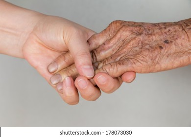 Hand of Young woman holding the hand of a senior woman