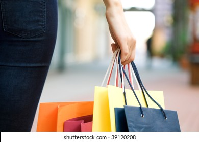 hand of young woman with multi-coloured bags with purchases