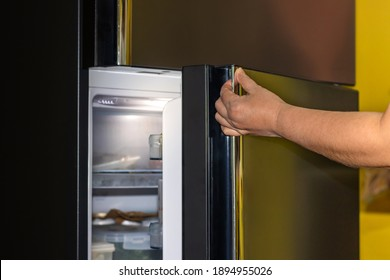 Hand of a young woman is opening a refrigerator door,closeup,Space for text