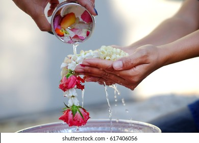 Hand of young woman pour water and flowers on the hands. older women and happy for the songkran festival. concept gives blessing in Songkran day Thailand