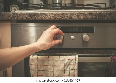 The hand of a young woman is turning the knob on a stove