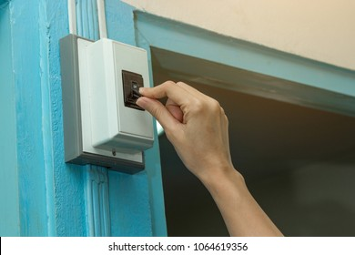 Hand of young woman turning off circuit breaker in home