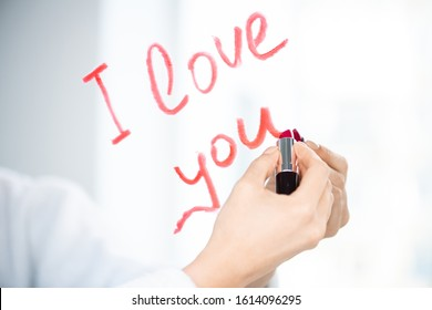 Hand of young woman writing love message with red or crimson lipstick on mirror in the morning
