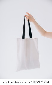 hand of young women with white cotton bags in hand on a white background. mock up, copy space