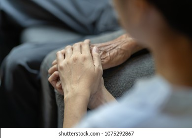 Hand of younger woman holding hand elderly man, helping hands, take care for elderly concept.