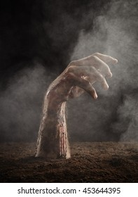 Hand of zombie in blood and dirt climbs out of the ground