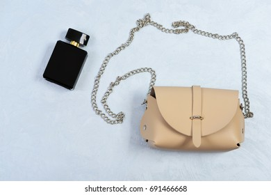 Handbag for women and black bottle of scent, top view. Purse in light beige color and perfume. Fashion and glamour concept. Accessories in modern style on light grey or white texture background