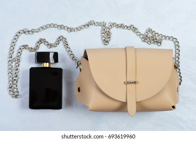 Handbag for women and black bottle of scent, top view. Fashion and style concept. Purse in light beige color with chain and perfume. Accessories in modern style on grey or white texture background