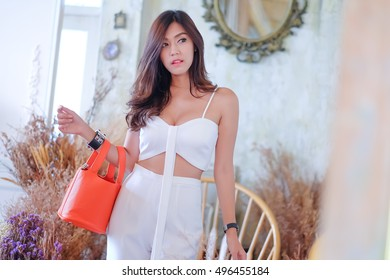 Handbags, business people, executives, a beautiful girl poses with a commitment to stand with the women fashion handbags.,Lighting with sun flare
