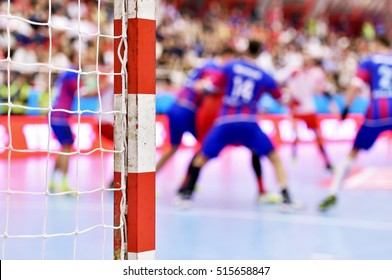 Handball match scene with goalpost and players in the background