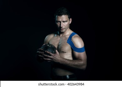 Handball player posing in studio with shoulder tape and ball