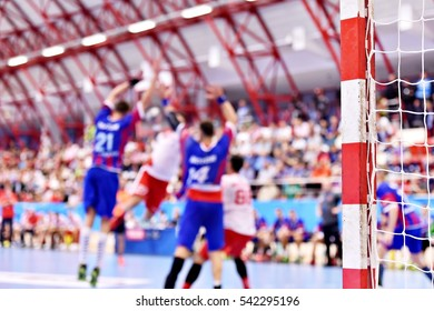 Handball unfocused match scene with goalpost and players in the background