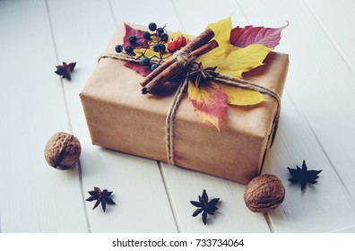 Handcraft gift box in the white wooden table. Autumn frame with gift, autumn leaves, cinnamon sticks, anise stars and nuts. Holiday gift on Thanksgiving