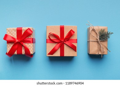 Handcraft gift boxes wrapped in brown recycled paper with red ribbons and rope on blue background, top view, copy space