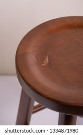 Handcrafted dark brown wooden backless stool on white background isolated