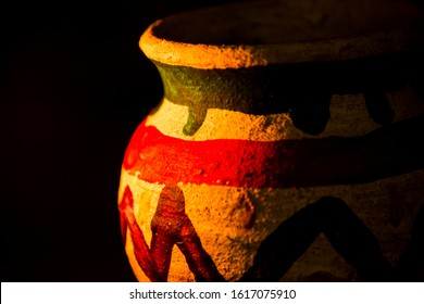 Handcrafted earthen pot again dark background. Clay vase made out of mud on dark background.