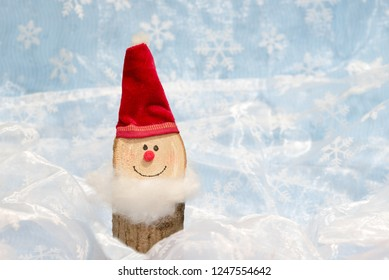 handcrafted funny santa gnome, made of wood. with red velvet stuff. white textile background with blurry snowflake pattern