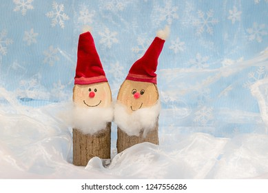 handcrafted funny santa gnomes, made of wood. with red velvet stuff. white textile background with blurry snowflake pattern