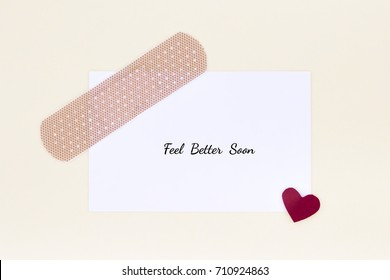 Handcrafted get well soon, feel better soon card  on yellow cream background. Cool and simple. Adorable paper pieced bandage.Top view and flat lay.