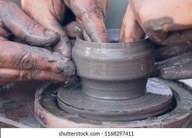 Handcrafted, Hands make clay. Master teaches the student to make pitcher on pottery wheel. Master class on modeling of clay on potter's wheel. Teaching traditional crafts