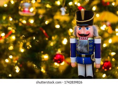 Handgefertigte Nutcracker Figurine mit beleuchtetem Weihnachtsbaum im Hintergrund