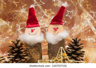 handcrafted santa gnomes made of wood and christmas background with golden stars and cones