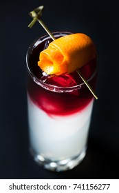 A handcrafted specialty alcoholic vodka&wine cocktail  in a tall glass on dark background