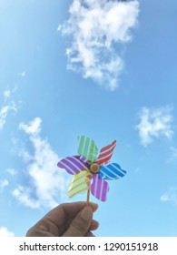 Handcrafted windmill pinwheel in woman hand against the background of sky and cloud