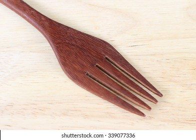 Handcrafted wooden kitchen utensils with a fork and spoons in two sizes lying on a wood surface with copyspace